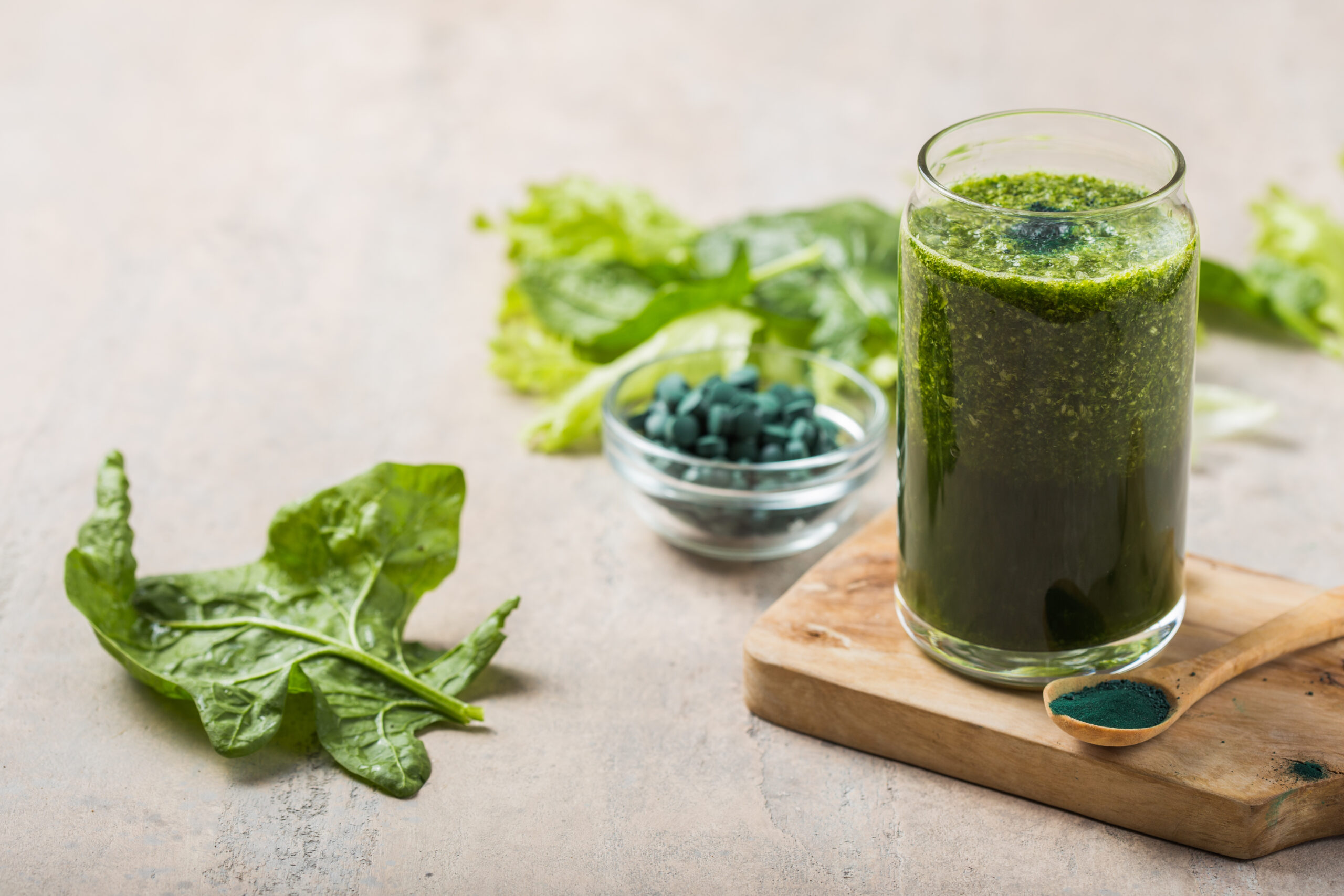 Green smoothie with spirulina. Young barley and chlorella spirulina. Detox superfood.Fresh green smoothie in a blender. Top view. Freshly prepared vegetarian smoothies
